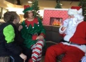 santa and his elf talk with student