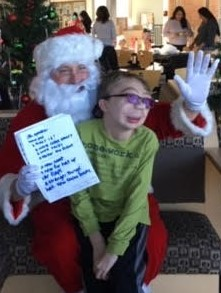 santa waves and holds a christmas list with a student on his lap